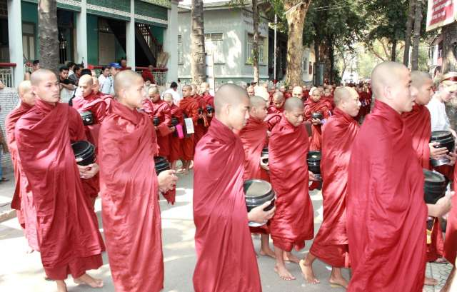A group of red robed Buddhist monk walking through the street.